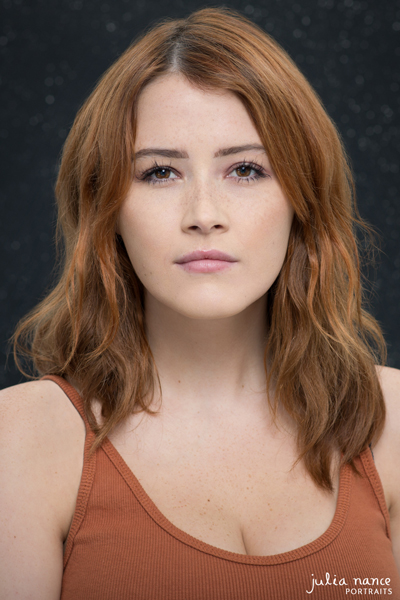 Melbourne Actor Headshot of redhead woman with a burn orange top on. She has a moody expression and the photograph has a dark background.
