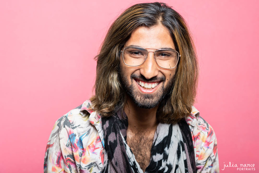 Personal Branding Headshot of man wearing floral patterned shirt and glasses with a bright pink background