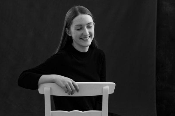 Black and white studio portrait of Julia Nance, smiling with eyes closed sitting on a white chair.