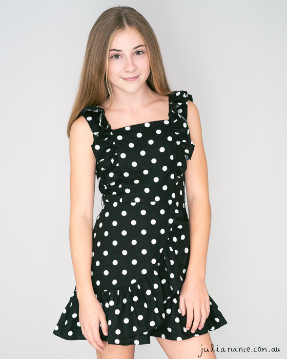 Melbourne actor headshot of young girl on grey background wearing a black polka dotted dress
