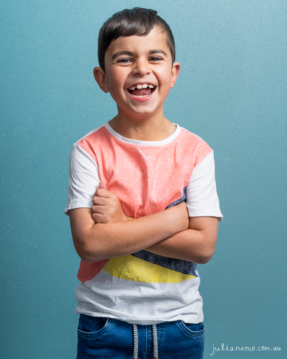 Young Melbourne boy laughing in studio on a blue background for his actor and model headshots