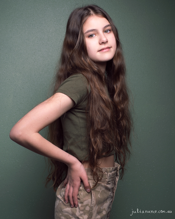 young melbourne actress standing with green background for an updated actor headshot and model portfolio