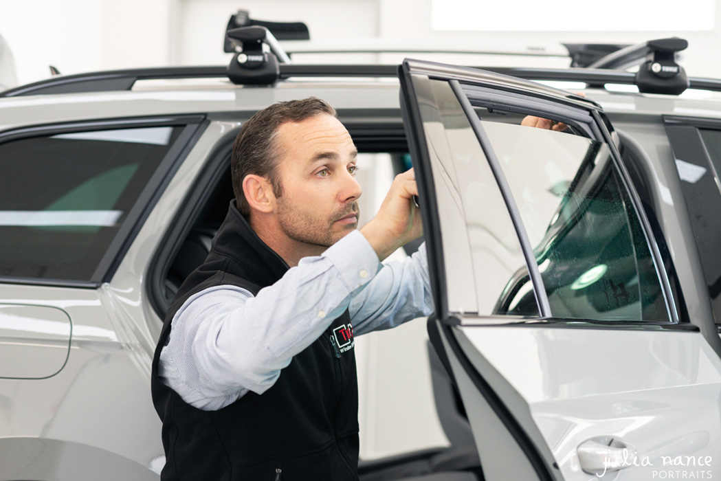 Personal branding photograph of worker tinting a car window
