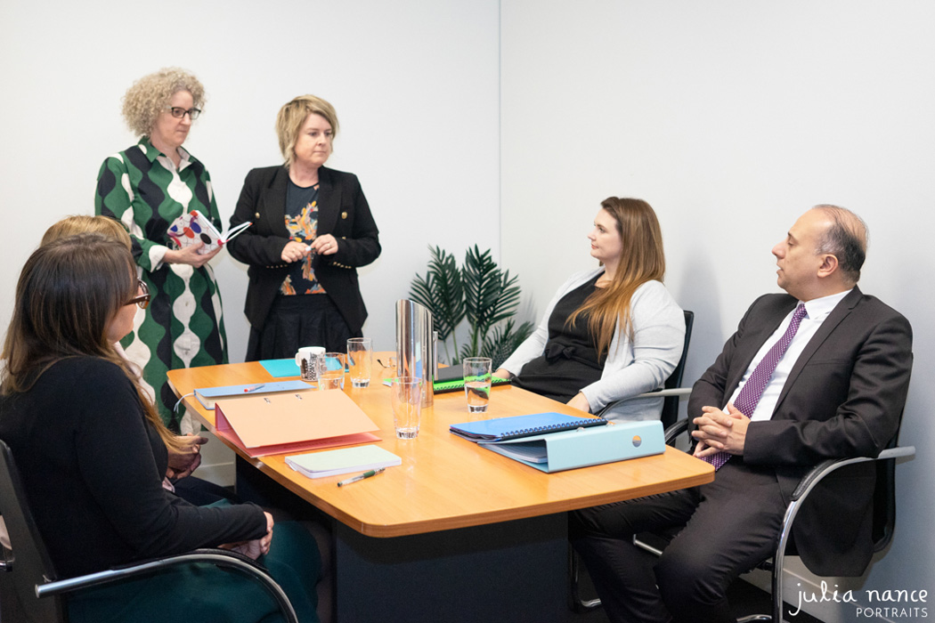 Personal Branding corporate photograph of an office team having a meeting in a conference room. On-site corporate portrait photograph taken by Julia Nance Portraits