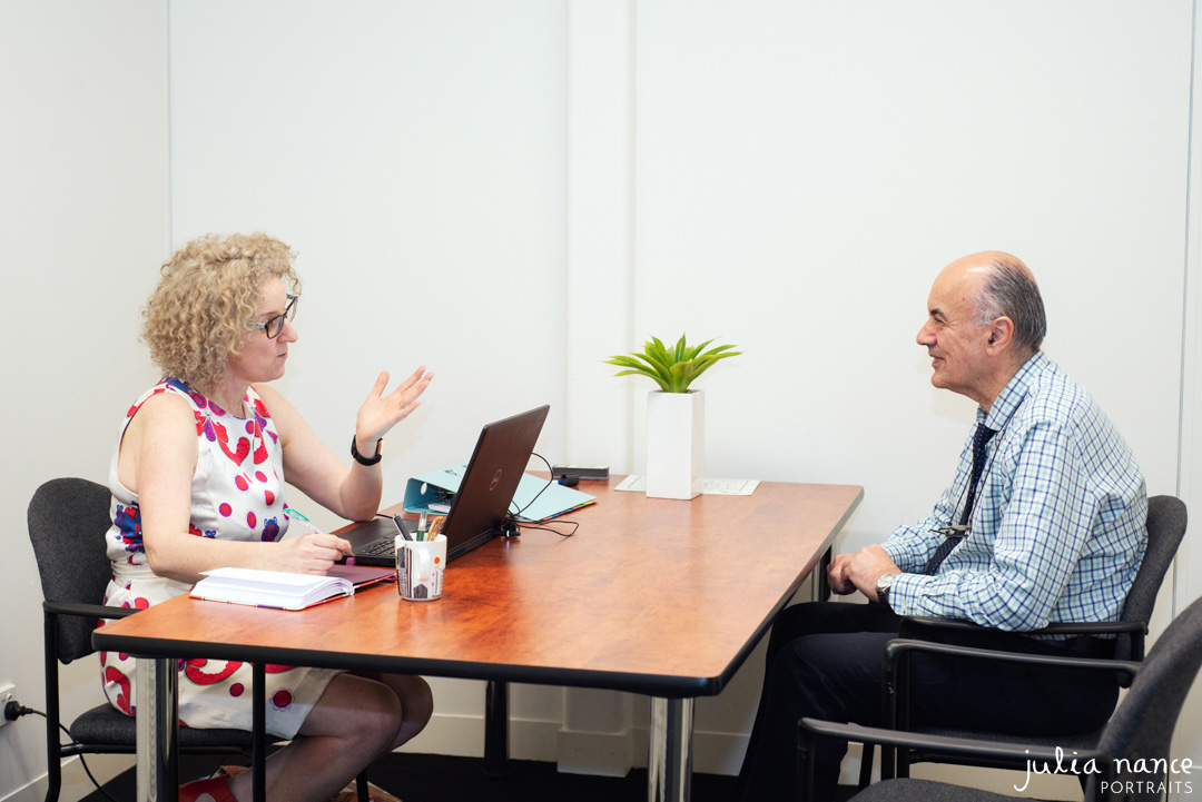 Personal branding photography of two people having a meeting while sitting at a desk. On-site corporate portrait photograph taken by Julia Nance Portraits