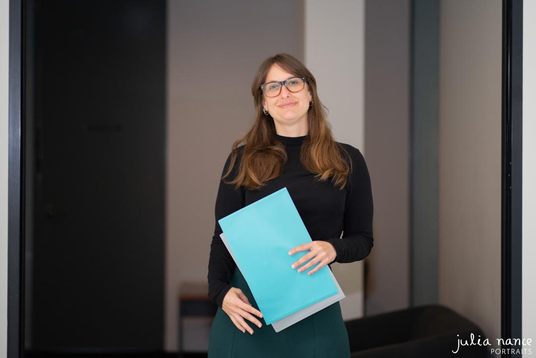 Personal branding corporate portrait of woman holding folders in workplace. On-site corporate portrait photograph taken by Julia Nance Portraits